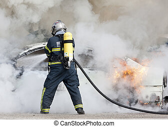 fireman in fire - a firefighter putting out a car that was...
