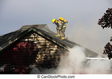 Fireman on top of a burning house - Fireman on the roof of...