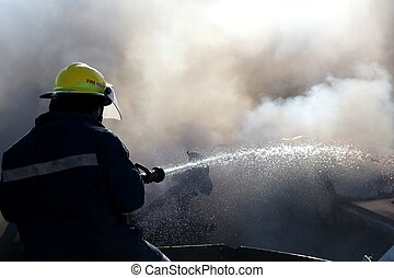 Fireman Putting Out Fire - Fireman spraying water on a burnt...