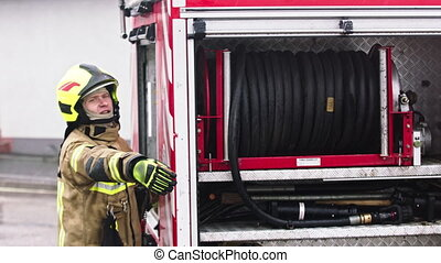 Fireman standing in front of the fire truck ready to unroll the hose