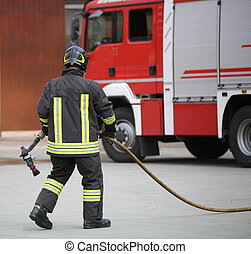 fireman with a hose after extinguishing a fire - fireman ...