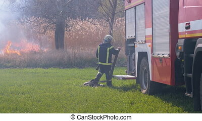 Fireman with a Fire Hose in a Forest near a Fire Truck Prepares to Extinguish a Fire. Burnt grass. Smoke rise. Spring. Slow Motion. Fireman in equipment Puts out a forest fire.
