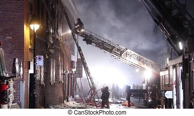 Fireman on top of ladder directing operator near building fire