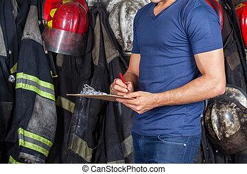 Fireman Writing On Clipboard - Midsection of fireman writing...