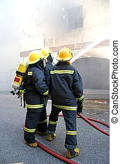 Firemen Fighting Fire - Firemen fighting a fire in a burning...