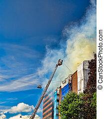 Firemen on a ladder extinguishing fire