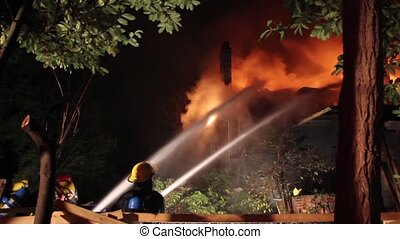 Firemen with hoses putting water on house fire at night