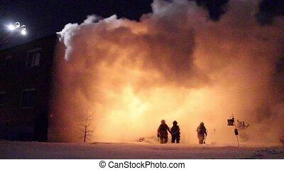 Firemen walking out of blaze cloud - Firemen in silhouette...