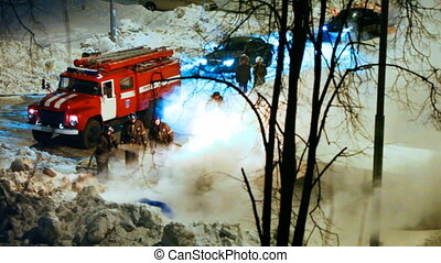 firemen watered with hose put out the fire near road