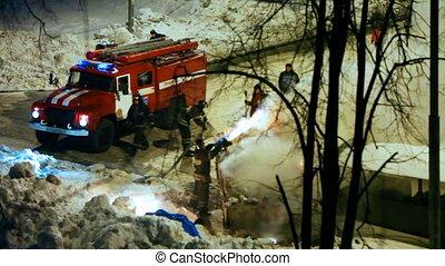 firemen with firetruck liquidate fire in box of garbage near...
