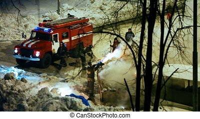 firemen with firetruck liquidate fire in box of garbage near...