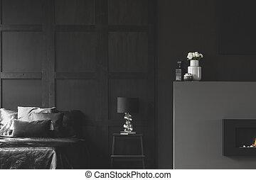 Fireplace in black bedroom interior