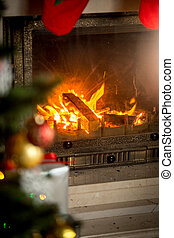 Fireplace with with burning wood logs decorated for Christmas