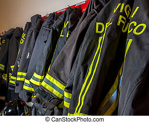 Fireproof suits of a team of firefighters ready to be worn for an emergency in a fire house