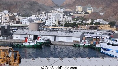 fireship sailing in seaport of Muscat, Oman, moutains in...