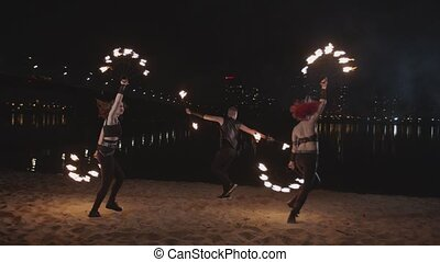 Fireshow artists juggling with fire on riverside - Skillful...