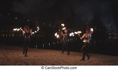 Fireshow artists turning around juggling fire outdoors -...