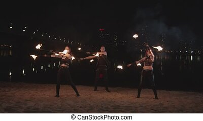 Fireshow performers juggling staves on riverside - Two...
