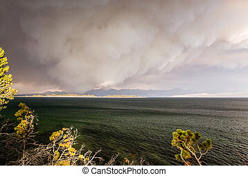 Smoke resembling a thundercloud billows from a nearby forest fire as the wind drives the wildfire toward the shoreline of Lake Yellowstone.