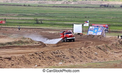 Firetruck on rally cross track in russian province wets the road to prevent dust