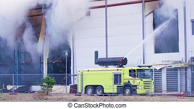 Firetruck trying to get control over a fire in industrial...