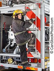 Firewoman Climbing Truck At Fire Station