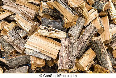Firewood background - chopped firewood on a stack.