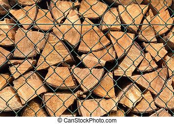 Firewood behind a green grid