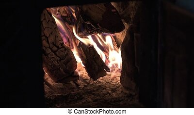 Firewood burns in the fireplace to heat the house.