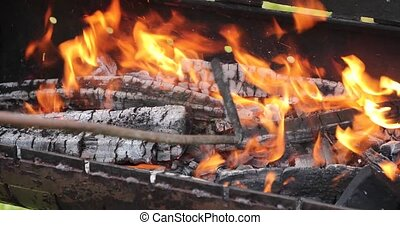 firewood fire in a brazier stirs with an iron stick.
