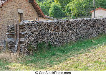 Firewood for heating lies along wall of bricks house. Wood heating and stone houses are traditional in village of Bourgogne, France.