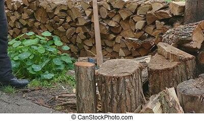 Firewood logs splitting using axe - Lumberjack chopping...