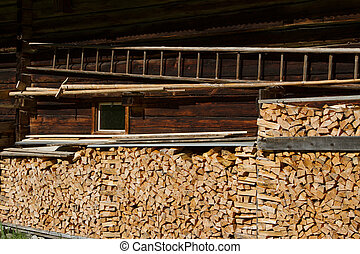 Firewood stacked by the alpine hut. Rustic farming scene.
