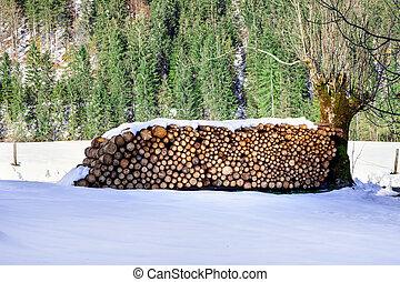 Firewood stacked. Winter alpine rural scene.