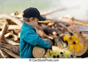 Young village boy bringing hard firewood in front of woodpile