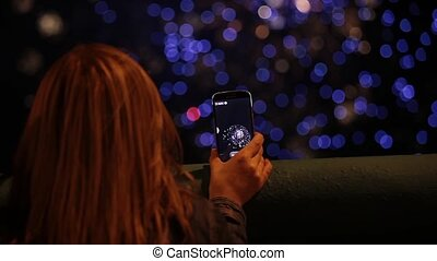 Firework pyrotechnic show - Girl using smartphone to record...