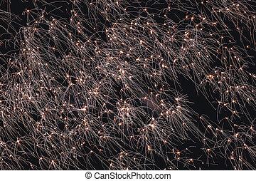 Firework sparkles exploding in bright light