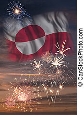 Holiday sky with fireworks and flag of Greenland, independence day