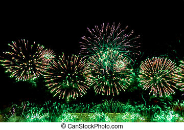Fireworks at New Year abstract holiday background. Green salute on black background.