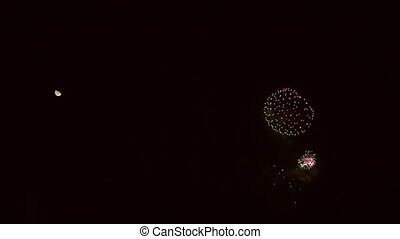 Fireworks explosions and moon in super slow motion