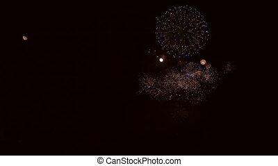 Fireworks explosions and moon in super slow motion against...