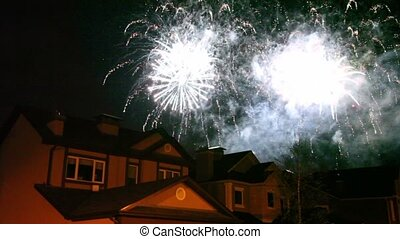 Fireworks glisten at dark sky over roofs of few houses