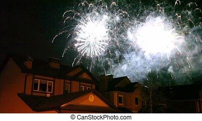 Fireworks glisten at dark sky over roofs of few houses