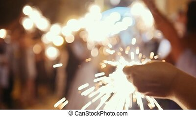 Fireworks in hands of guests - wedding evening, close up