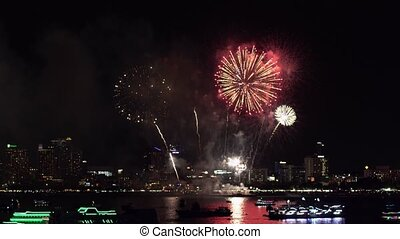 Fireworks over cityscape by the beach and sea surrounding...
