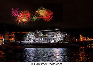 Fireworks over colorful holiday lights on a home