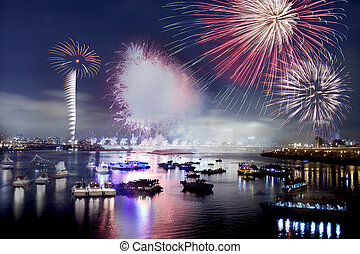 Fireworks - Fireworks firing up into the sky with a boat on...