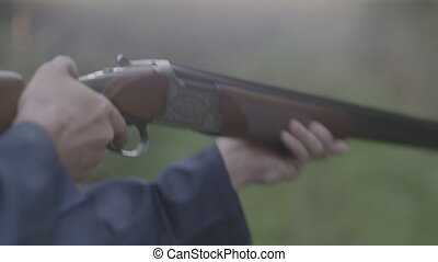 Close up of someone firing an over under double barrel shotgun, and then opening it to eject the empty shells