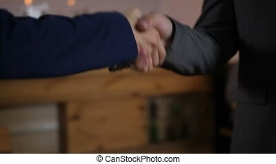 Close-up of firm handshake of two male businessmen for trusted partnership indoors. Confident male entrepreneurs in formalwear shaking hands after signing successful agreement.