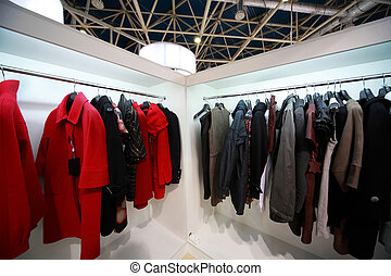 Firm outer clothing hangs at demonstration stands in...